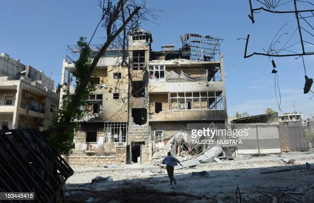 A Syrian rebel runs across a heavily damaged street to dodge sniper fire during clashes with government forces in the Saif alDawla district of the...