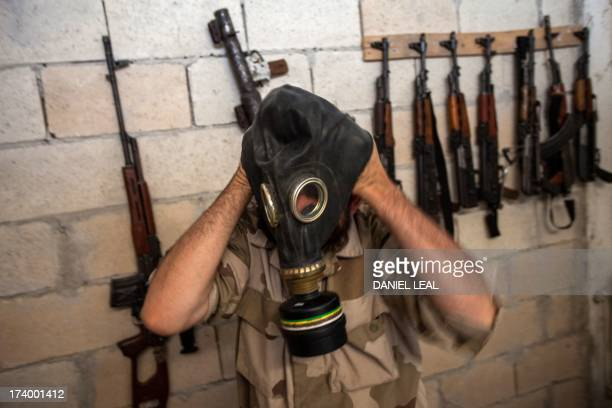 A Syrian rebel tries on a gas mask seized from a Syrian army factory in the northwestern province of Idlib on July 18 2013 Western countries say they...