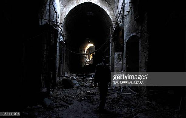 A Syrian rebel walks at a destroyed section of the Umayyad Mosque complex in the old city of Aleppo hours before the Syrian army retook control of it...