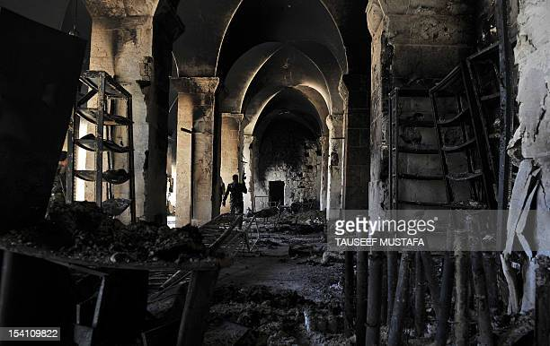 A Syrian rebel walks inside a burnt section of the Umayyad Mosque in the old city of Aleppo hours before the Syrian army retook control of the...