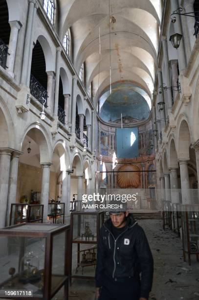 A Syrian rebel walks past damaged display cases inside a former church turned into a film museum which was shelleld by government forces in Aleppo's...