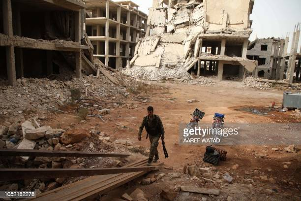 Syrian rebelfighter from the National Liberation Front enters a building in the rebelheld alRashidin district of western Aleppo's countryside near...