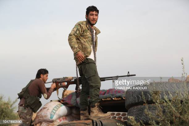A Syrian rebelfighter from the National Liberation Front gather on the frontline with regime forces inside the demilitarised zone in the south east...