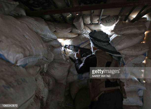 A Syrian rebelfighter from the National Liberation Front holds a machine gun at a position fortified with sandbags near the frontline in the...