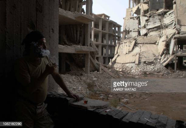 Syrian rebelfighter from the National Liberation Front stares at a damaged street in the rebelheld alRashidin district of western Aleppo's...