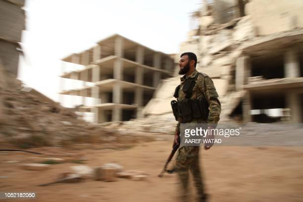 Syrian rebelfighter from the National Liberation Front walks in a street in the rebelheld alRashidin district of western Aleppo's countryside near...