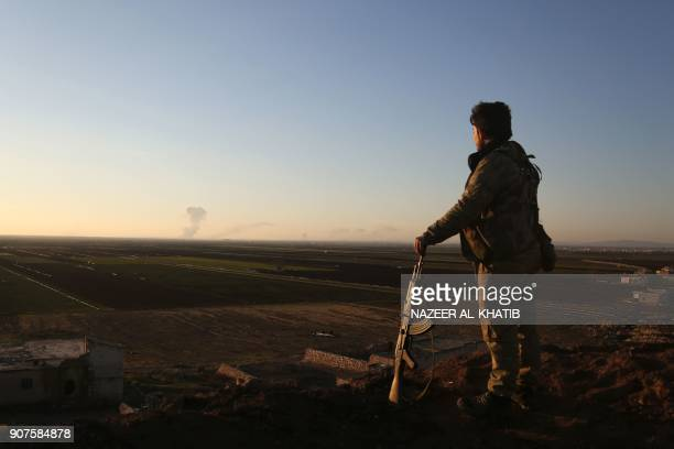 Syrian rebelfighter stands in the Tal Malid area north of Aleppo as he watches smoke billow from a Kurdish People's Protection Units position in the...
