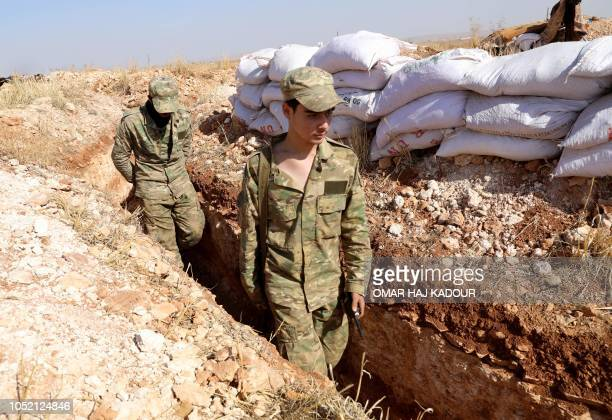TOPSHOT Syrian rebelfighters from the National Liberation Front walk through a trench at the frontline facing regime areas in the southern...