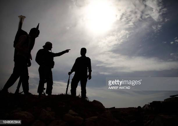 TOPSHOT Syrian rebelfighters with the National Liberation Front stand on a hill overlooking regimeheld areas in northwestern countryside of Aleppo...