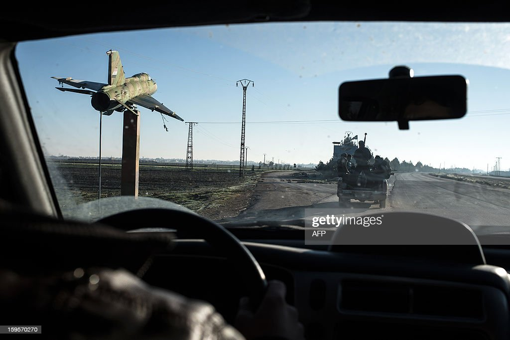 Syrian rebels drive past the shell of a military plane near the Abu Baker brigade in Albab, 30 kilometres from the northeastern Syrian city of Aleppo, on January 16, 2013. Universities were closed across Syria to mark a day of mourning called after twin blasts tore through an Aleppo campus while students were writing exams, killing at least 87 people.