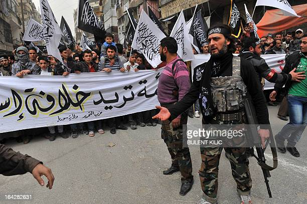 Syrian rebels stand guard as protesters wave Islamist flags during an antiregime demonstration in the northern city of Aleppo on March 22 2013 The UN...
