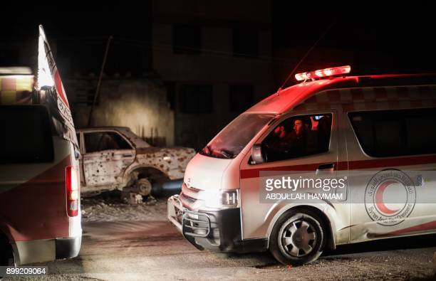Syrian Red Crescent ambulances queue to take patients on board on the second night of an evacuation operation coordinated with the International...