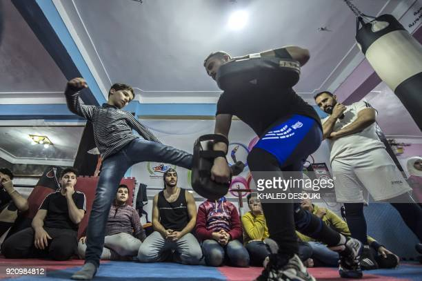 TOPSHOT Syrian refugee Amir alAwad watches as Adel Bazmawi teaches martial arts to youth at the academy in Egypt's second city of Alexandria on...