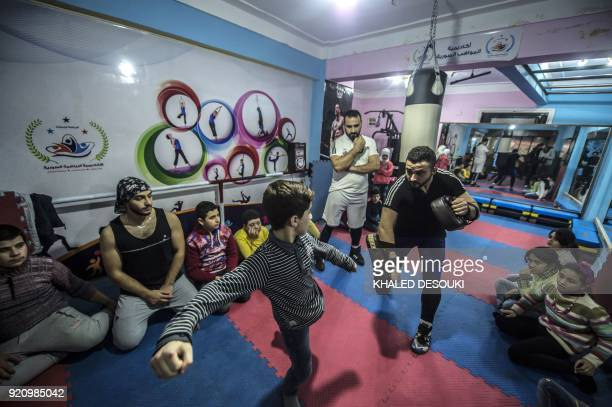 Syrian refugee Amir alAwad watches as Adel Bazmawi teaches martial arts to a youth at the academy in Egypt's second city of Alexandria on January 4...