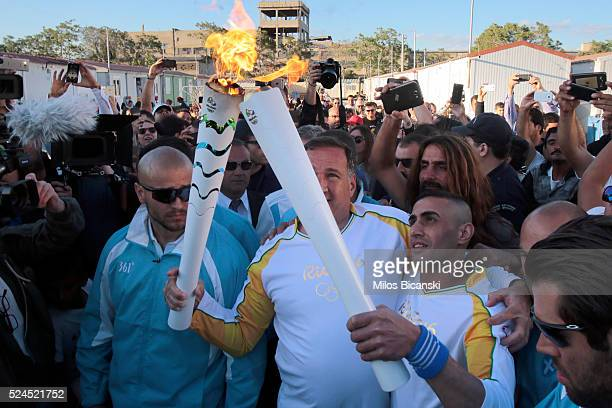Syrian refugee athlete Ibrahim AlHussein receives the Olympic flame from the head of Greece's Olympic Committee Spyros Capralos at the Elaionas camp...