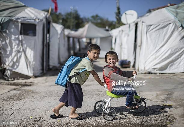 Syrian refugee boy fled from her home due to civil war pushes his friend on bike in Yayladagi YIBO camp in Hatay province of Turkey on October 25 2015