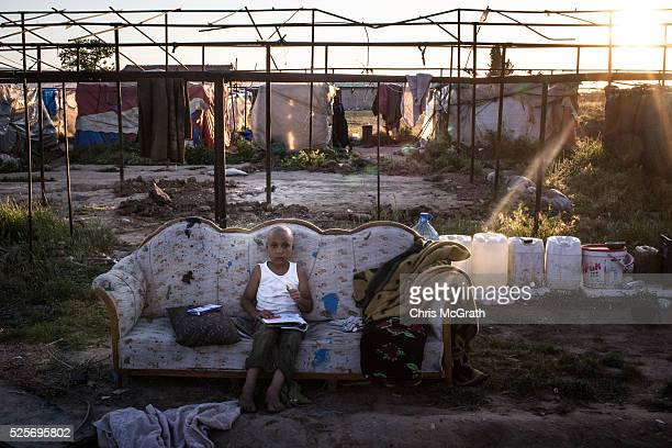 Syrian refugee boy is seen resting on a couch outside his home at a tent camp on the outskirts of Izmir on April 28 2016 in Izmir Turkey For many...