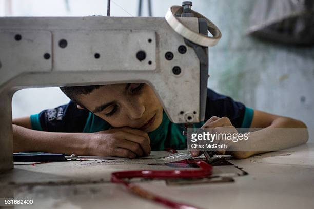 Syrian refugee boy makes shoe parts at a Turkish owned shoe workshop on May 16 2016 in Gaziantep Turkey Since fleeing the war and after the new EU...