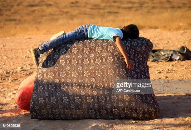 Syrian refugee boy rests on the side of the road as he returns to Syria with his family after crossing the Jordanian border near the town of Nasib in...