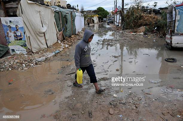 A Syrian refugee boy walks in a muddy alley at a makeshift camp in the village of Kfarkahel in the Kura district near the northern city of Tripoli on...