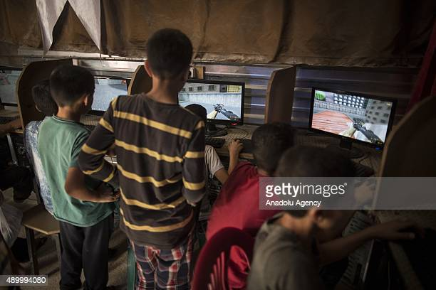 Syrian refugee boys play war games on computers at an internet cafe at a tent city in the Akcakale District of Sanliurfa Turkey on September 24 2015...