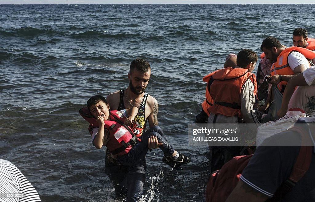 A Syrian refugee carries a child out of an inflatable boat on the shores of Lesbos island in Greece on August 23, 2015.