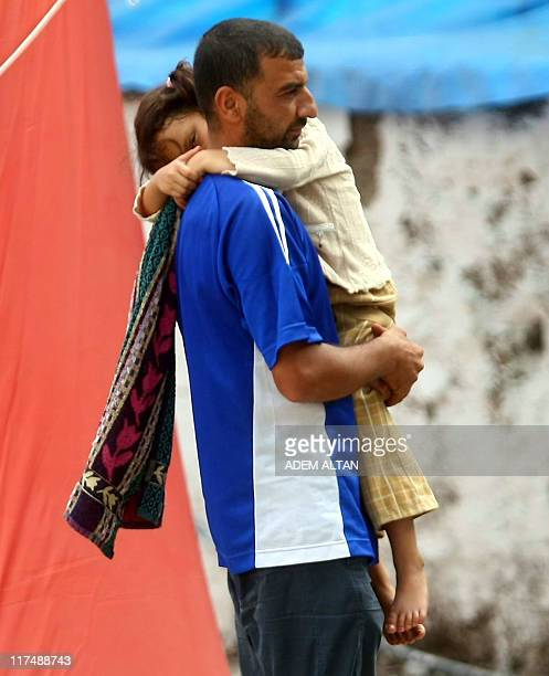 A Syrian refugee carries a girl in a camp near the Turkish border town of Yayladagi in Hatay province on June 27 2011 Turkish officials said on June...