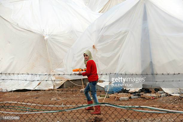 A Syrian refugee carries oranges at the Reyhanli refugee Camp in Antakya on March 16 2012 Around 1000 Syrian refugees including a defecting general...