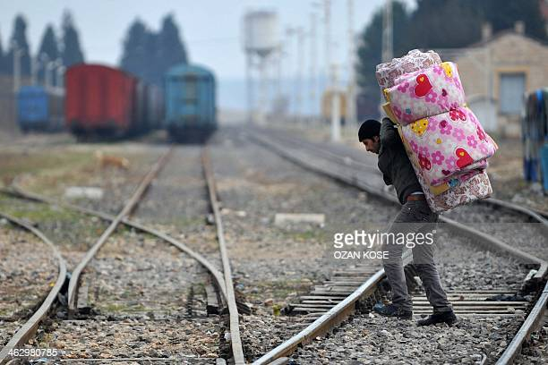 A Syrian refugee carrying his belongings passes over railway tracks after crossing the Syrian border on January 16 2014 in Karkamis near the town of...