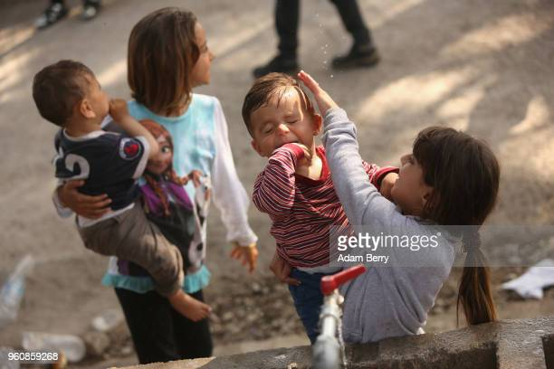 Syrian refugee child cleans her brother's face at the Moria refugee camp on May 20 2018 in Mytilene Greece Despite being built to hold only 2500...