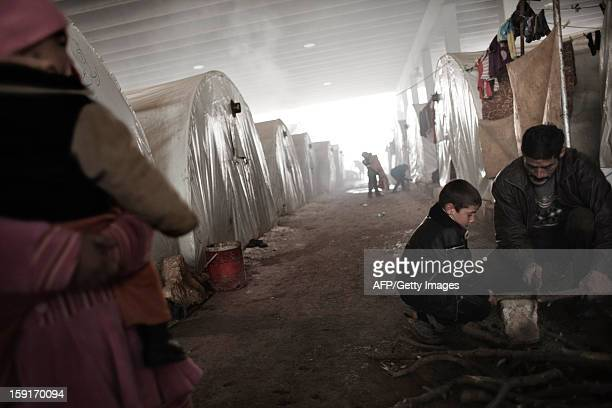 A Syrian refugee child helps a man to cut wood at a refugee camp near the northern city of Azaz on the SyriaTurkey border on January 9 2013 The...