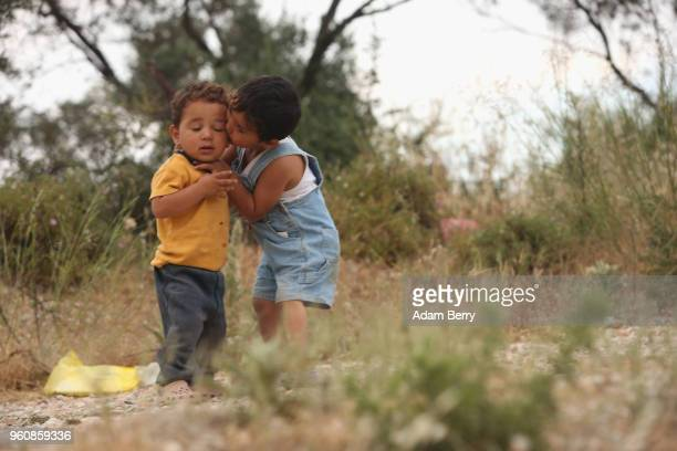 Syrian refugee child kisses her brother outside the Moria refugee camp on May 20 2018 in Mytilene Greece Despite being built to hold only 2500 people...