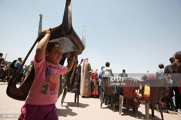 Syrian refugee child takes a chair as others perform sports activities in AL Azraq camp for Syrian refugees on April 30 2015 in AlAzraq Jordan On the...