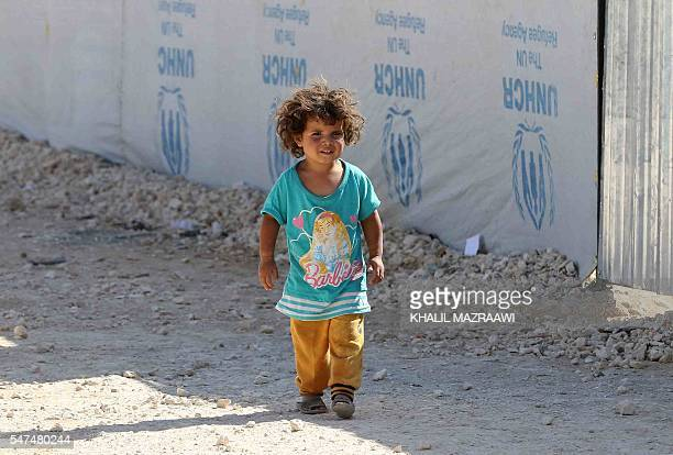 A Syrian refugee child walks at the Zaatari refugee camp located close to the northern Jordanian city of Mafraq near the border with Syria on July 14...