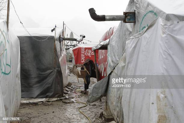 A Syrian refugee child walks in an alley past tents at an unofficial refugee camp in the village of Deir Zannoun in Lebanon's Bekaa valley on January...