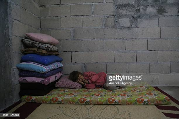 Syrian refugee child who fled from her home due to civil war rests at a house in Reyhanli district of Hatay on November 21 2015 Syrian refugee...