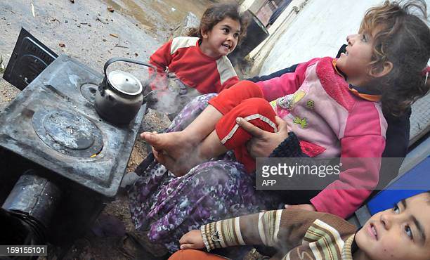 Syrian refugee children and their mother sit around a wood burning oven in Kfarkahel village in the Koura district close to the northern city of...