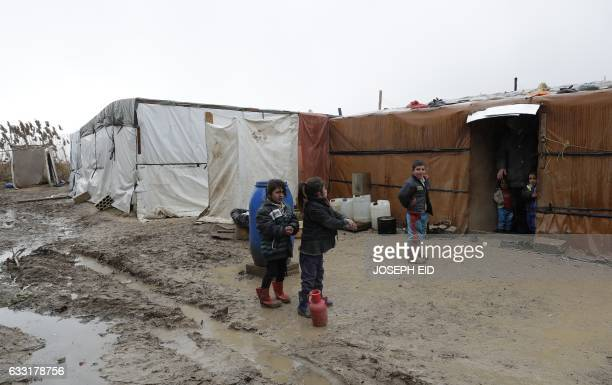 Syrian refugee children are seen outside their makeshift house at an unofficial refugee camp in the village of Deir Zannoun in Lebanon's Bekaa valley...