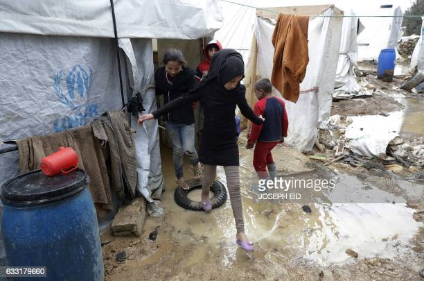 Syrian refugee children are seen trying to avoid mud as they walk at an unofficial refugee camp in the village of Deir Zannoun in Lebanon's Bekaa...
