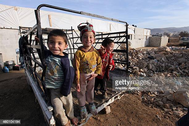 Syrian refugee children fled their homes due to the civil war in their country play on a car at Babel refugee camp in eastern Lebanese city of Arsal...