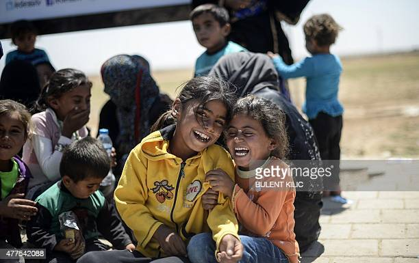 Syrian refugee children laugh as they sit on the side of a road that leads to the Akcakale border gate as they wait to return to their home in the...