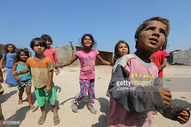 Syrian refugee children play at an unofficial refugee camp in the area of Arida north of Beirut on June 15 2015 Rights group Amnesty International...