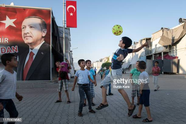 Syrian refugee children play in front of a poster of Turkey's president Recep Tayyip Erdogan at the Kahramanmaras refugee camp on September 19 2019...