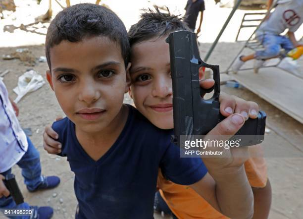 Syrian refugee children poses for a photo as they play on a street in the Palestinian Shatila refugee camp on the southern outskirts of the Lebanese...