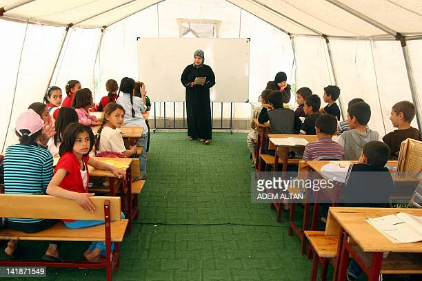 Syrian refugee children sit in a makeshift classroom at the Red Crescent camp in Boynuyogun village Hatay region on March 25 2012 The Boynuyogun camp...
