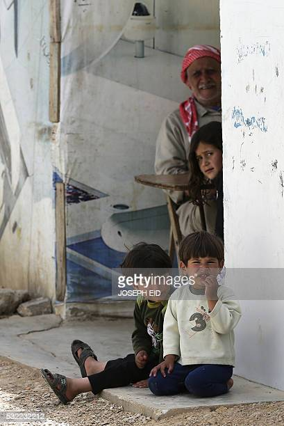 Syrian refugee children sit with their grandfather at an unofficial refugee camp in Lebanon's town of Bar Elias in the Bekaa Valley on May 13 2016...