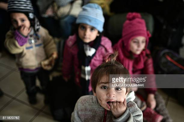 Syrian refugee children wait at the port terminal of Piraeus on February 23, 2016 upon the arrival of migrants and refugees from the Greek islands of...