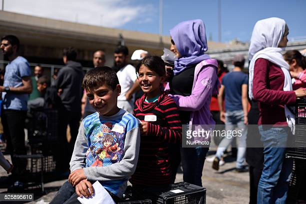 Syrian refugee children wait in line for food distribution in Pireas Port Athens on April 28 2016 Some thousands of refugees are still located in...