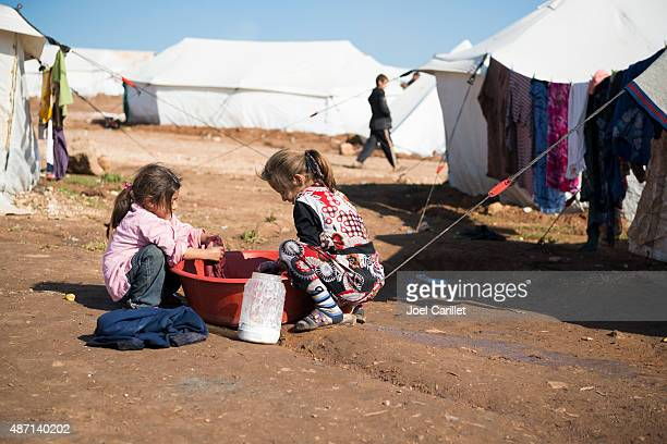 syrian refugee children washing clothes - war stock pictures, royalty-free photos & images