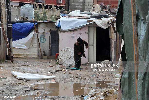 A Syrian refugee cleans the mud outside a tent at a makeshift camp in the village of Kfarkahel in the Kura district near the northern city of Tripoli...